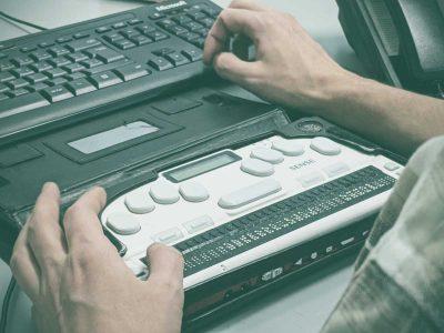 Blind man using a braille screen reader.